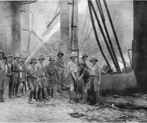 IWM photograph: THEY FOUGHT TO SAVE SALONIKA: Mr Collinson Owen emphasizes the great difficulty which confronted the troops in their endeavours to fight the Salonika fire. There were men in thousands, but for this sort of fighting there was a great deficiency of weapons. Above is a building that has been completely gutted, and a single hose pipe, the jet from which can be seen on the left of the photograph, is all that is available to quench the glowing ruins.