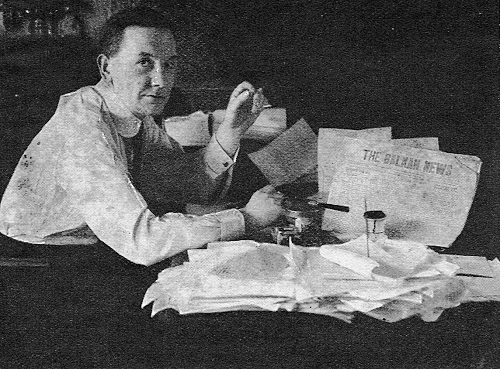 """IWM photograph: AT THE EDITOR'S DESK. Mr H. Collinson Owen at work in his office. In front of him is a copy of his paper, """"The Balkan News"""", which he edited so successfully."""