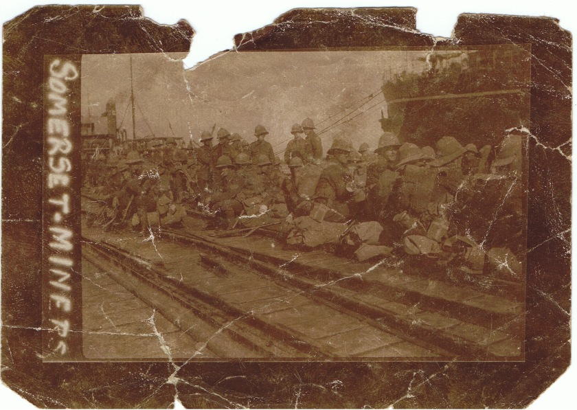 Image captioned 'Somerset Miners' showing British troops waiting on a quayside - believed to be Salonika - in sun helmets and service dress.