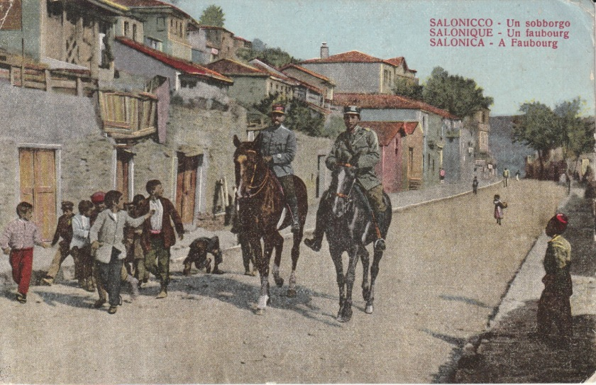 Hand-tinted postcard showing a suburb of Salonika, with children following two mounted soldiers or gendarmes.