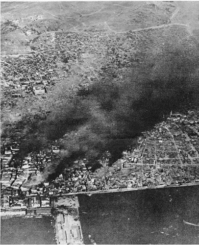 IWM photograph: WHEN SALONIKA WAS WIPED OUT BY FIRE. The great fire of Salonika started in the Jewish quarter and gradually crept down towards the sea front. Many of the refugees had fled to the quays to escape the fire, but the Navy came to the rescue. Lighters were brought alongside the quays and the terrified refugees were embarked with their baggage. By the time the flames had reached the waterside nearly all of them had been got away. About 4,000 houses were destroyed. This photograph was taken soon after the fire had started. In the foreground is the English quay.